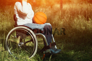 Woman in wheelchair with basket ball on her laps