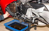 Motorbike in the a service station with oil Change - Serie repair workshop