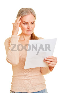 Frau liest Brief von Versicherung oder Behörde