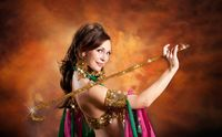Gorgeous woman bellydancer dancing in traditional bellydance costume over colored studio background.