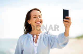 happy smiling woman taking selfie on summer beach