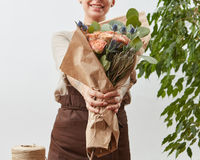 Smiling girl florist with beautiful bouquet in her hands on a light background with green leaves. Mother's Day holiday.