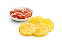 Round corn nacho chips and tomato dip. Yellow tortilla chips and salsa
