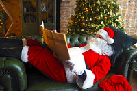 Santa claus reading business newspaper while sitting on sofa