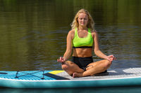 Young dutch woman meditates on SUP in water