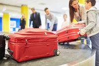 Familie und Reisende am Gepäckband holen Koffer ab