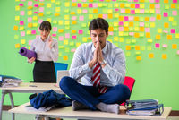 Man and woman in the office with many conflicting priorities in