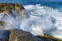 Waves crashing over rocks with water drops