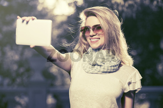 Young fashion woman taking a selfie with tablet computer outdoor