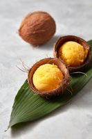 yellow sorbet ice cream in the coconut shell on stone background