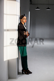 Slender african american girl wearing business clothes and glasses standing by the wall with her hands crossed.