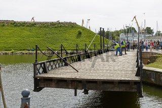 Unidentified workers perform manually turn of wrought Swing bridge built in 1855 in Castle port of Klaipeda across moat Dassel between Castle Pond and river Dange. It is only mechanism of its type in Baltic countries