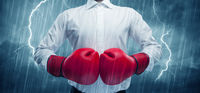 Businessman boxing in rain