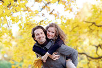Smiling couple play in autumn forest