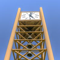 Clock tower with bells under a blue sky