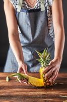Cut pineapple. Girls hands hold fruit on a brown wooden table with copy space. Ingredient for dessert
