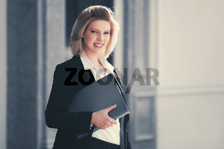 Happy young business woman with file folder at office building