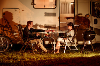 Adult couple clinking glasses of wine. Family vacation travel RV, holiday trip in motorhome, Caravan car Vacation.