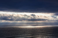 rays of sun through the clouds over ocean