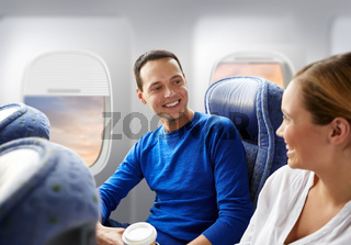 happy passengers with coffee talking in plane