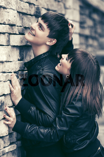 Happy young fashion couple in leather jackets at the brick wall