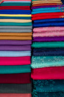 Folded sheets of colourful material lined up on display on a market stall for sale.