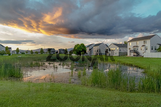 Scenic sunset view of a pond amid grasses and homes under cloudy sky