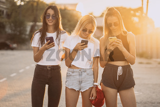 Three attractive women are standing on car parking with smartphones