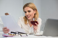 Cheerful business woman holding glass of wine in bed