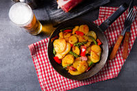 Fried potatoes with smoked bacon, green asparagus and paprika.