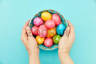 Hände halten Ostereier im Korb zu Ostern