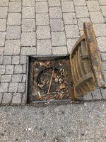 Einlaufschacht zur Straßenentwässerung, der durch Erde verstopft ist