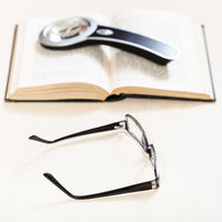 spectacles and loupe on open book on pale table