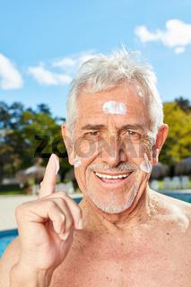 Senior cremt Gesicht mit Sonnenmilch ein