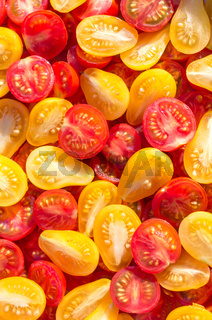 Fresh halves of Mexican cherry tomatoes. Sliced yellow and red cherry tomatoes.Background of many colorful cherry tomatoes. Cherry tomatoes top view.