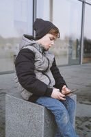 7 year old boy playing with smartphone outdoors in winter