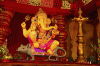 An idol of Lord Ganesha, sitting on his vehicle - a mouse, Guruji Talim Mandal, Pune, Maharashtra, India.