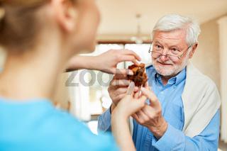 Altenpflegerin betreut Senior Mann mit Demenz