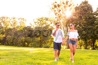 Beautiful young couple walking together in the park
