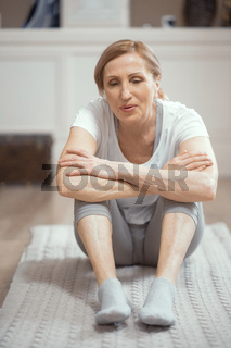 Smiling woman is having a rest sitting after practicing yoga