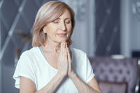Happy woman holds hands put in prayer pose. Meditation