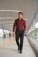 Young handsome Hispanic businessman walking on the footbridge
