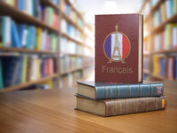 Learn French concept. French dictionary book or textbok with flag of France and Eiffel tower on the cover in the library.