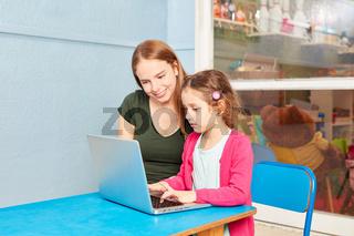 Mädchen und Erzieherin am Laptop PC