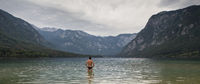 Man going to swim in freezing cold lake Bohinj, Alps mountains, Slovenia, on tranquil overcast morning