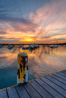 Beautiful sunset across the bay with moored yachts and boats