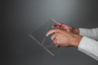 Hands holding futuristic transparent tablet pc