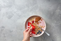 Preparation of a healthy pink smoothie made of strawberry with yoghurt and porridge on a concrete background