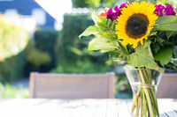 Colorful bright sunflower in vase in a green summer garden on wooden table. Selective focus.