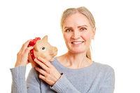 Seniorin mit Sparschwein als Altersvorsorge